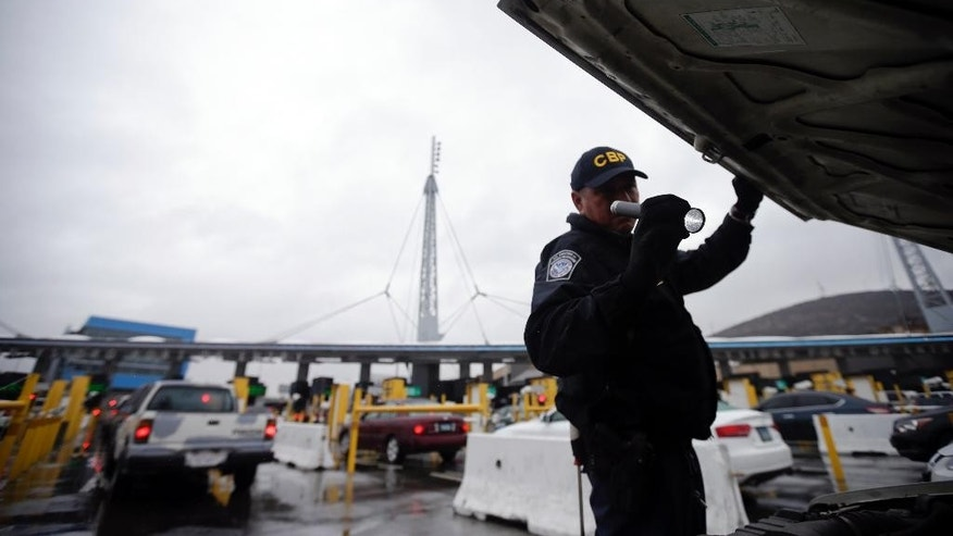 FILE - In this Dec. 3, 2014 file photo, a U.S. Customs and Border Protection (CBP) officer checks under the hood of a car as it waits to enter the U.S. from Tijuana, Mexico through the San Ysidro port of entry in San Diego. A group of First Amendment attorneys is suing the Trump administration over access to data showing how often citizens and visitors had their electronic devices searched and the contents catalogued at the border. (AP Photo/Gregory Bull, File)