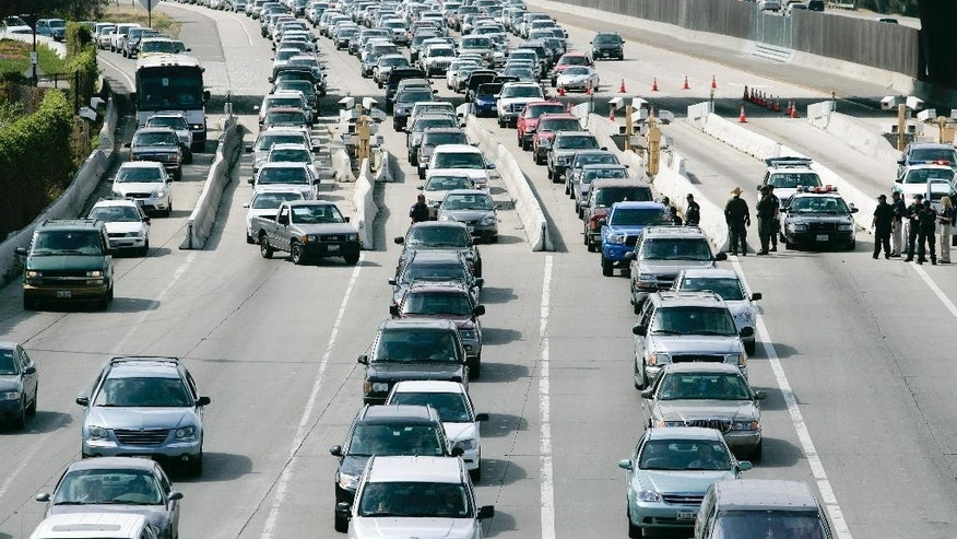 FILE - In this April 23, 2009 file photo, U.S. border officials set-up a road block to search cars as traffic backs up on Interstate-5 before crossing the border into Mexico from the U.S. at the San Ysidro Port of Entry in San Diego. A group of First Amendment attorneys is suing the Trump administration over access to data showing how often citizens and visitors had their electronic devices searched and the contents catalogued at the border. (AP Photo/Denis Poroy, File)