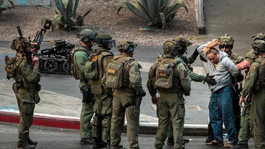 A suspect surrenders to SWAT officers after being barricaded for many hours on a bus after a fatal shooting in the vehicle earlier today which down the busy tourism corridor near the Cosmopolitan hotel-casino in Las Vegas, Saturday, March 25, 2017. Las Vegas Police officer Larry Hadfield said just before 3:30 p.m. that the man had a handgun and surrendered without incident.  (L.E. Baskow/Las Vegas Sun via AP)