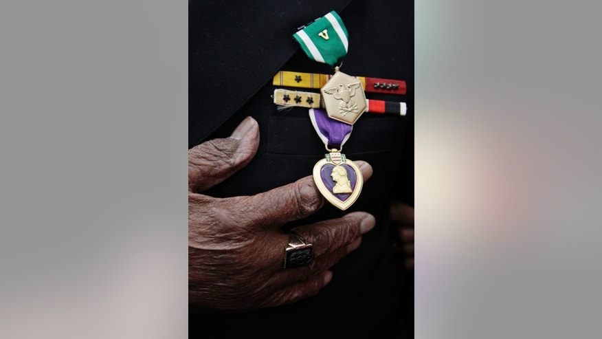 FILE - In this Jan. 17, 2012 file photo, Carl Clark, 95, shows off the prestigious Navy and Marine Corps Commendation Medal with Combat Distinguishing Device, top in green, and the Purple Heart, in purple below, during a ceremony with Navy Secretary Ray Mabus at Moffett Field in Mountain View, Calif., for his heroism on May 3, 1945 when his ship, the USS Aaron Ward, was hit by six Kamikaze planes and two bombs during WWII. Clark, of California, who was denied a medal of honor for his heroism during World War II for more than six decades because he was black, has died at age 100. Clark's daughter, Karen Clark Collins, said Tuesday, March 28, 2017, her father died March 16 at a Veteran's Administration hospital in Menlo Park. (AP Photo/Paul Sakuma, File)
