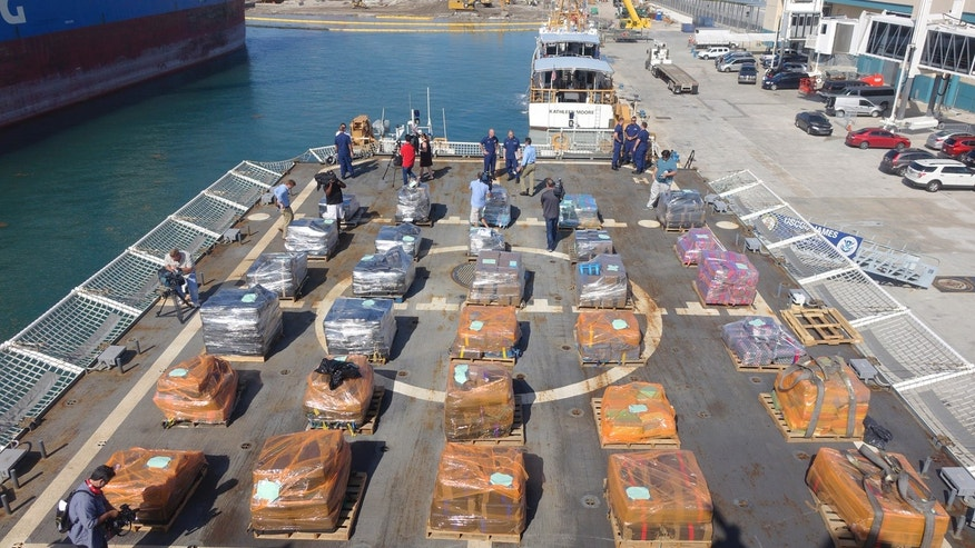 U.S. Customs and Border Patrol officers alongside Coast Guard personnel prepare to offload cocaine from the Coast Guard Cutter James, Tuesday, March 28, 2016, at Port Everglades in Fort Lauderdale, Fla.
