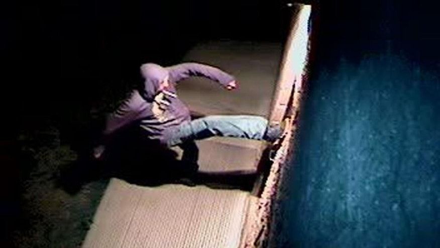 In this Sunday, March 26, 2017, still image from a video surveillance camera, a suspect is shown during the vandalizing of a mosque near Colorado State University in Fort Collins, Colo. Police are asking for the public's help in identifying the person who overturned benches, broke windows and threw a Bible into a mosque near Colorado State University, a case they are investigating as a hate crime. (Fort Collins Police Department via AP)
