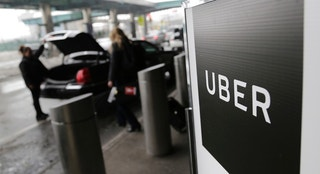 FILE - In this Wednesday, March 15, 2017, file photo, a sign marks a pickup point for the Uber car service at LaGuardia Airport in New York. Uber's first report on employee diversity shows low numbers for women, especially in technology positions. Uber's report doesn't count drivers as employees. (AP Photo/Seth Wenig, File)