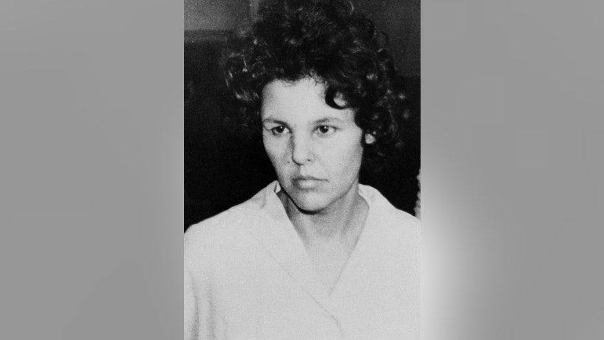 FILE - In this Oct. 21, 1981 file photo, Judith Clark is taken into police custody in Nanuet, N.Y. Nearly 10,000 people have signed a petition urging the New York state Parole Board to deny the release of the ex-radical who drove a getaway car in the 1981 Brinks armored car robbery that left three dead. Republican Sen. Patrick Gallivan said he would deliver the petition Wednesday, March 29, 2017. Clark's parole hearing is set for next month.  (AP Photo/David Handschuh, File)