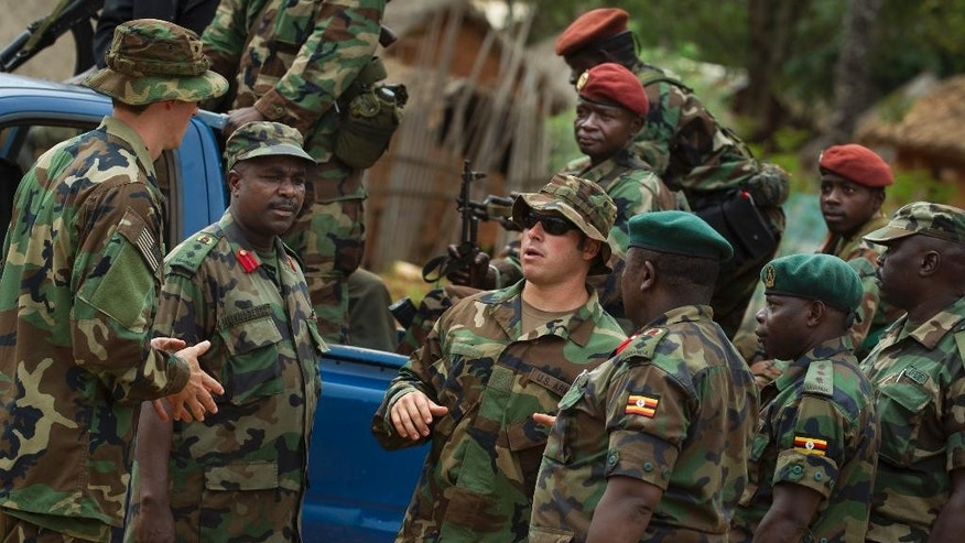 FILE - In this Sunday, April 29, 2012 file photo, U.S. Army special forces Master Sergeant Eric, center, who would only give his first name in accordance with special forces security guidelines, speaks with troops from the Central African Republic and Uganda, in Obo, Central African Republic, where U.S. special forces have paired up with local troops and Ugandan soldiers to seek out Joseph Kony's Lord's Resistance Army (LRA). A rebel in charge of communications for warlord Joseph Kony has surrendered to Ugandan forces, the military said Thursday March 30, 2017, shortly after the U.S. indicated it was pulling out of the international manhunt for one of Africa's most notorious fugitives. (AP Photo/Ben Curtis, File)