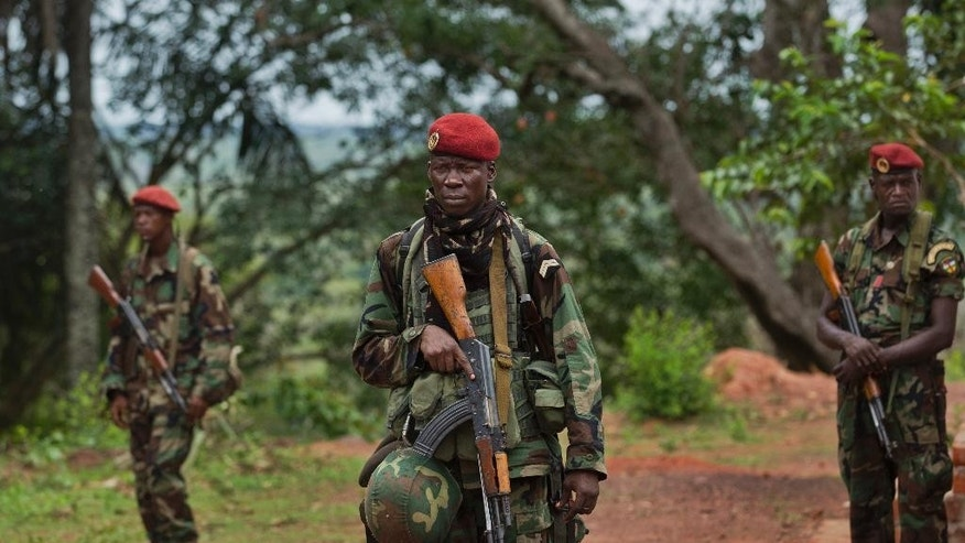 FILE - In this Sunday, April 29, 2012 file photo, troops from the Central African Republic stand guard at a building used for joint meetings between them and U.S. Army special forces, in Obo, Central African Republic, where U.S. special forces have paired up with local troops and Ugandan soldiers to seek out Joseph Kony's Lord's Resistance Army (LRA). AA rebel in charge of communications for warlord Joseph Kony has surrendered to Ugandan forces, the military said Thursday, March 30, 2017, shortly after the U.S. indicated it was pulling out of the international manhunt for one of Africa's most notorious fugitives. (AP Photo/Ben Curtis, File)
