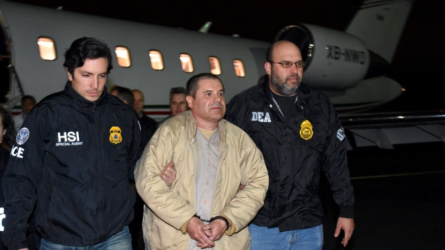 "Authorities escort Joaquin ""El Chapo"" Guzman from a plane to a waiting caravan of SUVs at a in Ronkonkoma, N.Y.  airport on Jan. 19, 2017."