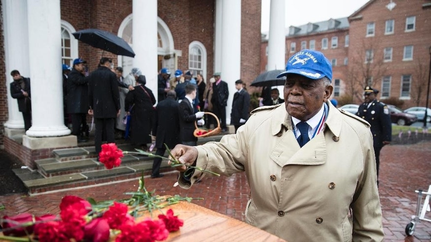 Tuskegee Airman Eugene J. Richardson Jr., places a flower on the casket containing the remains of his comrade John L. Harrison, Jr., after Harrison's a funeral mass at the Chapel of the Four Chaplains in Philadelphia, Friday, March 31, 2017.  Harrison Jr. became one of America's first black military airmen, one of nearly 1,000 pilots who trained as a segregated unit with the Army Air Forces at an airfield near Tuskegee, Ala. (AP Photo/Matt Rourke)