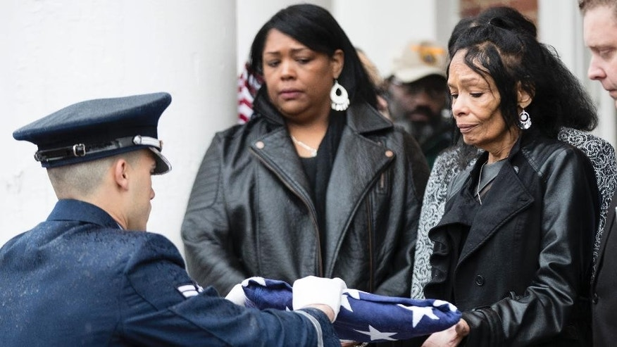 Tanzy Williams, (granddaughter) center, looks on as an Airman hands Joan Harrison, right, the flag that covered her father John L. Harrison Jr. casket at the Chapel of the Four Chaplains in Philadelphia, Friday, March 31, 2017.  Harrison Jr. became one of America's first black military airmen, one of nearly 1,000 pilots who trained as a segregated unit with the Army Air Forces at an airfield near Tuskegee, Ala. (AP Photo/Matt Rourke)
