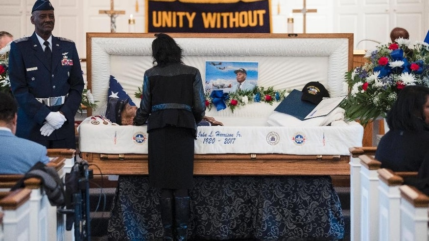 Joan Harrison pays her respects to her father John L. Harrison, Jr., ahead of his funeral mass at the Chapel of the Four Chaplains in Philadelphia, Friday, March 31, 2017.  Harrison Jr. became one of America's first black military airmen, one of nearly 1,000 pilots who trained as a segregated unit with the Army Air Forces at an airfield near Tuskegee, Ala. (AP Photo/Matt Rourke)