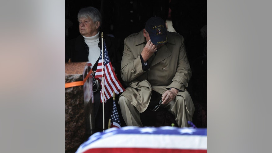 Relative Robert Whelihan wipes away a tear during the graveside for service U.S. Army Cpl. Jules Hauterman Jr., a Korean War soldier, who was laid to rest in St Jerome's Cemetery in Holyoke, Mass., on Friday, March 31, 2017. Hauterman was a medic attached to the 31st Regimental Combat Team who went missing in December 1950 during fierce fighting against Chinese forces at the Chosin Reservoir. His remains were discovered in 1954 but were not positively identified until last year. At left is Whelihan's wife Mary, (Dave Roback/The Republican via AP)
