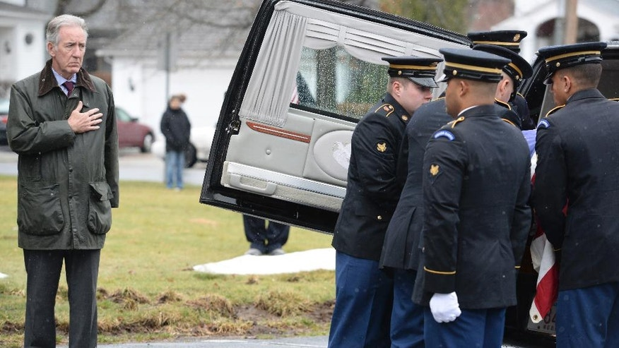 Congressman Richard E. Neal, left, looks on as an honor guard places the remains of U.S. Army Cpl. Jules Hauterman Jr., a Korean War soldier, into a hearse outside of the Blessed Sacrament Church after a funeral Mass in Holyoke, Mass., on Friday, March 31, 2017. Hauterman was a medic attached to the 31st Regimental Combat Team who went missing in December 1950 during fierce fighting against Chinese forces at the Chosin Reservoir. His remains were discovered in 1954 but were not positively identified until last year. (Dave Roback/The Republican via AP)