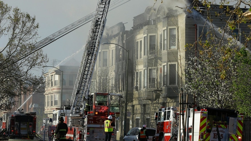 FILE - In this Monday, March 27, 2017 file photo, firefighters battle an early morning apartment fire in Oakland, Calif.