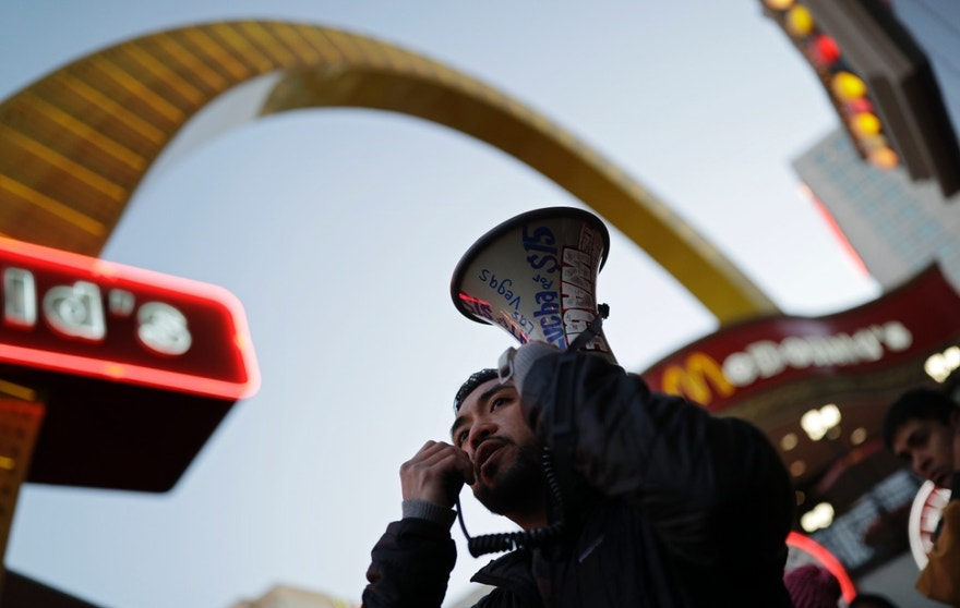 A.J. Buhay speaks on a bullhorn as he and others protest near a McDonald's restaurant along the Las Vegas Strip, Tuesday, Nov. 29, 2016, in Las Vegas. The protest was part of the National Day of Action to Fight for $15. The campaign seeks higher hourly wages, including for workers at fast-food restaurants and airports. (AP Photo/John Locher)