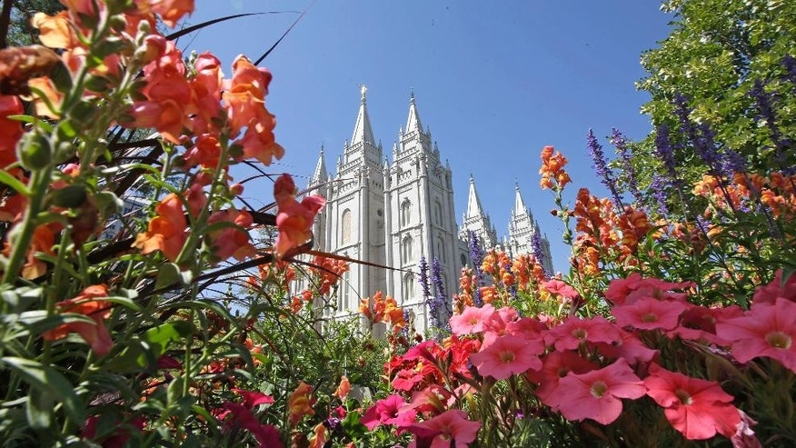 FILE - This Aug. 4, 2015, file photo, flowers bloom in front of the Salt Lake Temple, at Temple Square, in Salt Lake City. Mormons will hear guidance and inspiration from the religion's top leaders during a church conference this weekend in Salt Lake City as well as getting an update about church membership statistics. (AP Photo/Rick Bowmer, File)