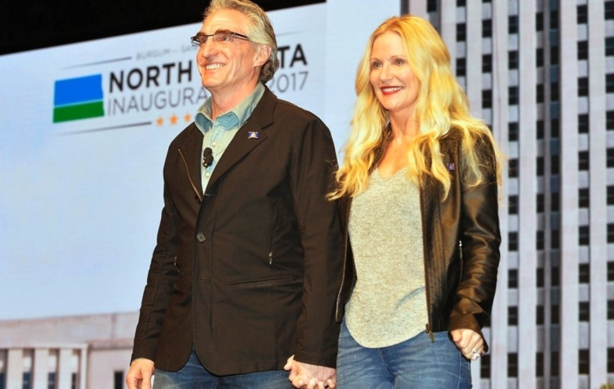 "FILE - In this Jan. 4, 2017 photo, North Dakota Gov. Doug Burgum and first lady Kathryn Helgaas Burgum greet the crowd at the governor's inauguration celebration in Bismarck, N.D. Burgum's preference for wearing jeans got him booted from the North Dakota Senate floor Wednesday, Feb. 15, 2017, while he was posing for a photo with some high school students. A spokesman says the governor ""meant no disrespect to the chamber rules."" (Will Kincaid/The Bismarck Tribune via AP, File)/The Bismarck Tribune via AP)"