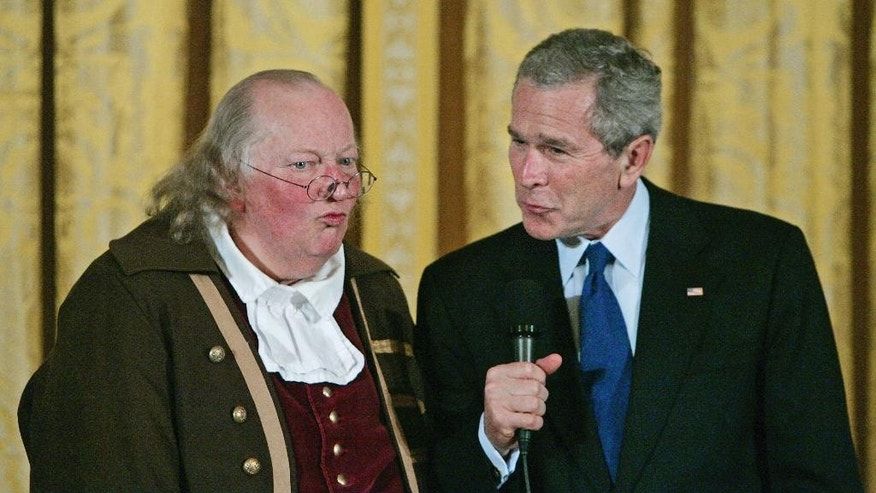 FILE – In this March 23, 2006, file photo, President George W. Bush, right, speaks after a performance by re-enactor Ralph Archbold, left, portraying Benjamin Franklin to mark the 300th anniversary of Franklin's birth on Jan. 17, 1706, in the East Room of the White House in Washington. Archbold, who portrayed Franklin in Philadelphia for more than 40 years, died Saturday, March 25, 2017, at age 75, according to the Alleva Funeral Home in Paoli, Pa. (AP Photo/Manuel Balce Ceneta, File)
