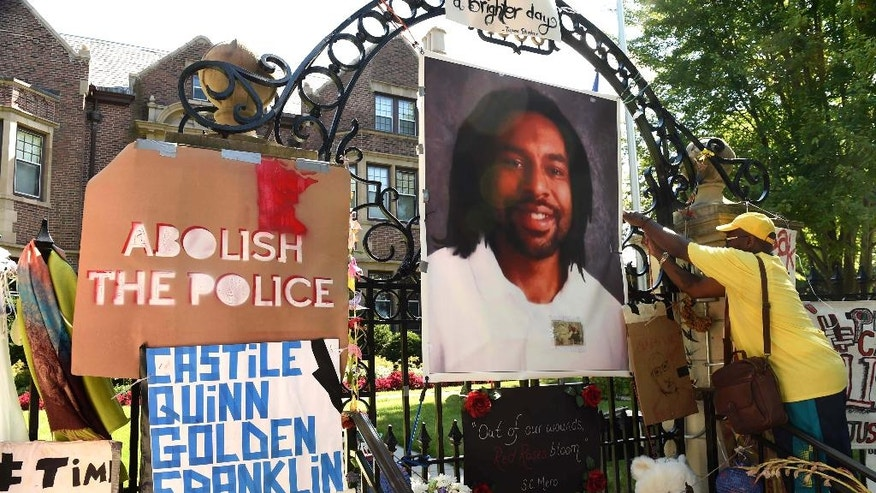 FILE - In this  July 24, 2016 file photo, King Demetrius Pendleton hangs a sign on the gate of the Governor's Residence next to a photograph of Philando Castile, in St. Paul, Minn.  Attorneys for St. Anthony police officer Jeronimo Yanez argued in court Tuesday, April 4, 2017,  that the officer cannot get a fair trial in Ramsey County, where Philando Castile was shot, because of pretrial publicity.  Yanez is charged with second-degree manslaughter and two other felonies in the death of the 32-year-old Castile, who was shot in Falcon Heights in July 2016. (Scott Takushi/St. Paul Pioneer Press via AP)