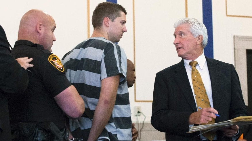 FILE – In this July 30, 2015 file photo, former University of Cincinnati police officer Ray Tensing, center, glances toward his lawyer Stewart Mathews, right, after entering not guilty pleas on charges of murder and voluntary manslaughter in the July 19, 2015, traffic stop shooting of Samuel DuBose, during Tensing's arraignment at the Hamilton County Courthouse in Cincinnati. Hamilton County, Ohio, Common Pleas Court Judge Leslie Ghiz was scheduled to meet with attorneys and prosecutors Tuesday, April 4, 2017, to discuss pretrial progress for Tensing's murder retrial set to begin May 25, 2017, after his first trial ended with a hung jury. (AP Photo/John Minchillo, File)