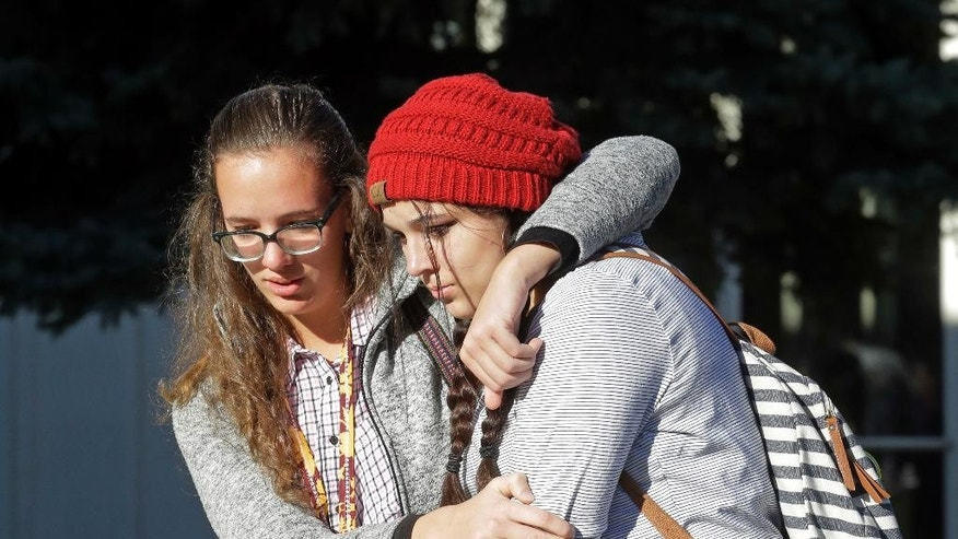 FILE - This Nov. 15, 2016, file photo, students Albany Cox, right, and Holly Hilton leave Mountain View High School where several students were stabbed, in Orem, Utah. One of five victims of a high school locker room stabbing in Utah says he no longer feels safe at school and is angry and confused about why he and others were attacked last November. The teenager spoke Tuesday, April 4, 2017, at a hearing in Orem in which the suspect signed off on an agreement that stipulates he'll face one count of aggravated attempted murder in adult court. He admitted to four other counts of aggravated attempted murder in juvenile court as part of the deal. (AP Photo/Rick Bowmer, File)