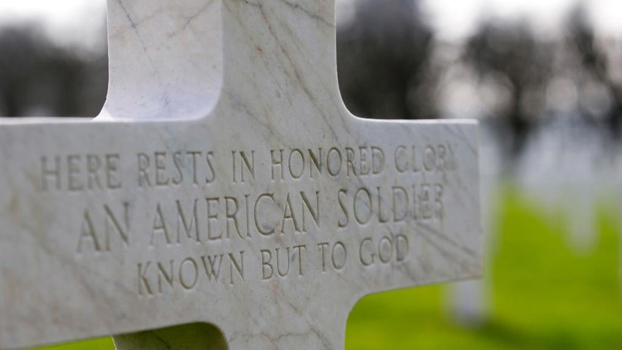 In this photo taken on Friday, March 24, 2017, A gravestone marker for an unknown soldier in the rows of crosses of American World War I soldiers at the Meuse-Argonne American cemetery in Romagne-sous-Montfaucon. The cemetery is the largest American cemetery in Europe. (AP Photo/Virginia Mayo)