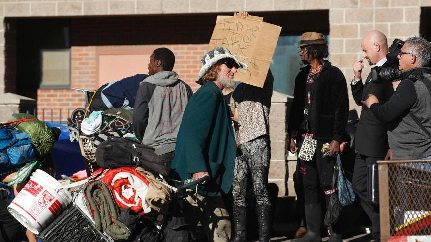 FILE - In this Nov. 15, 2016, file photo, an unidentified man drags his belongings away during a sweep of homeless people who were living on the sidewalks surrounding a shelter near the baseball stadium in downtown Denver. Three advocates for Denver's homeless are being tried and could face a year in jail for trying to camp outside city hall.  (AP Photo/David Zalubowski, File)