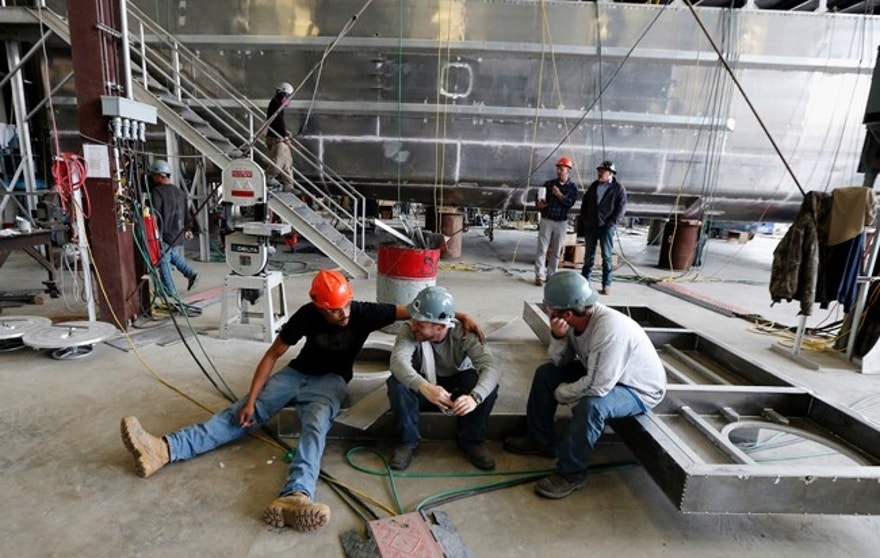 In this March 30, 2017 photo, workers take a break while working on one of several ferryboats being built for a new fleet of ferries for New York City, at the Metal Shark Shipyard in Franklin, La. The fleet is scheduled to launch this summer just a little more than a year after it was first proposed. (AP Photo/Gerald Herbert)