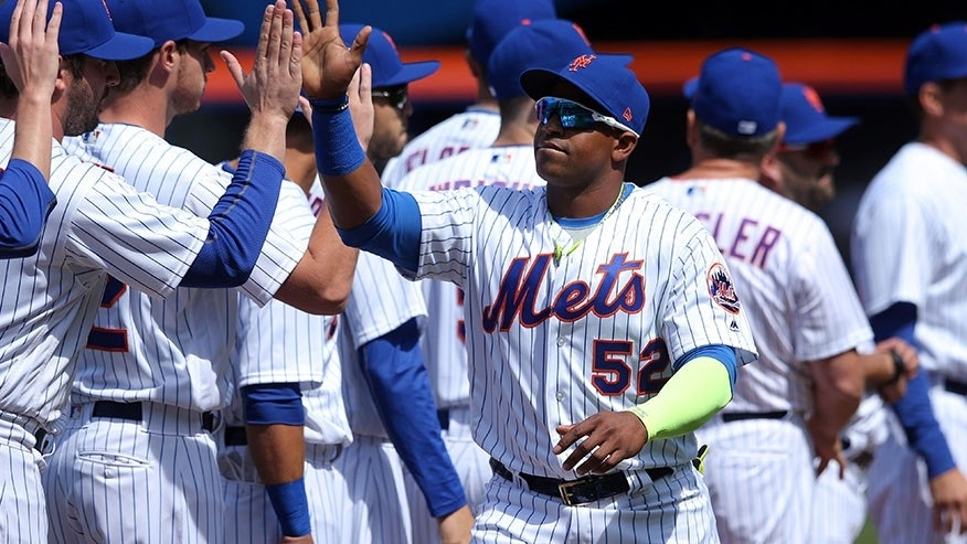 NY Mets' Yoenis Cespedes high fives teammates as he's introduced before a game against the Atlanta Braves Apr 3, 2017, in New York City.