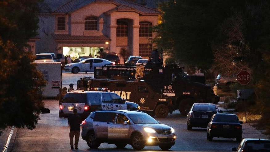 Las Vegas police and SWAT officers surround a home of Nicolai Howard Mork as they clear the property, Wednesday, April 5, 2017, in Las Vegas. Mork, who had been free on bail for three months while fighting explosives and firearms charges, was arrested late Wednesday on counts of terrorism and possession of weapons of mass destruction, authorities said. Mork was taken into custody at one of his homes in a southern Las Vegas neighborhood after police evacuated residents from several nearby homes. (AP Photo/John Locher)