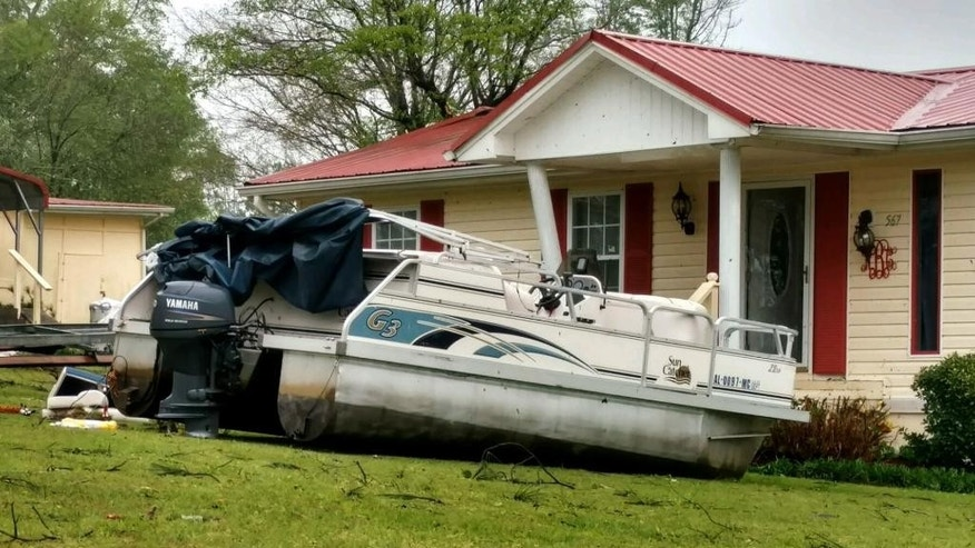 A pontoon boat sits in the front yard of a home in the Screamer community of Henry County, Ala., after a suspected tornado touched down in the county Wednesday, April 5, 2017. National Weather Service meteorologist Mark Wool said a suspected tornado touched down Wednesday in Henry County, Alabama, before crossing into Georgia. (Michele W. Forehand/Dothan Eagle via AP)