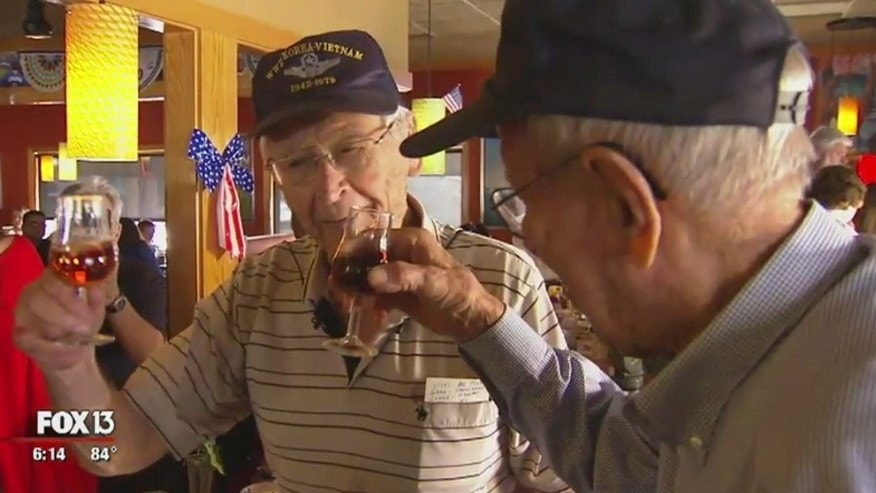 "Sanford ""Sandy"" Graves, left, and Marshall Clark, the last living pilots of the 451st Bomber Squadron, share a toast to their fallen comrades."
