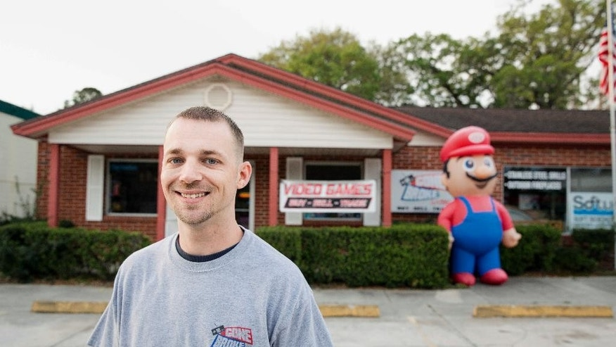 "In this undated photo provided by the Institute for Justice, Scott Fisher stands outside his video game store in Orange Park, Fla., a suburb of Jacksonville. A Florida city is saying ""game over"" to a business owner's decision to inflate a 9-foot-tall (2.7-meter-tall) Super Mario outside his shop. Fisher filed a federal lawsuit on Thursday, April 6, 2017, arguing that the town's ban violates his free speech. (Institute for Justice via AP)"