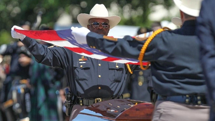 Members of the Harris County Honor Guard remove the American flag from the casket of Harris County assistant chief deputy constable Clint Greenwood  at the Second Baptist Church on Thursday, April 6, 2017, in Houston.  Greenwood was killed Monday by a gunman who stepped out from behind a dumpster as Greenwood arrived for work at a county courthouse east of Houston. The gunman is still on the run.  (Steve Gonzales/Houston Chronicle via AP)