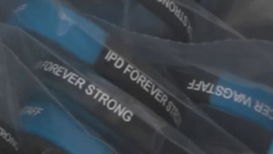 "The wristbands read ""IPD Forever Strong,"" with the officer's name."