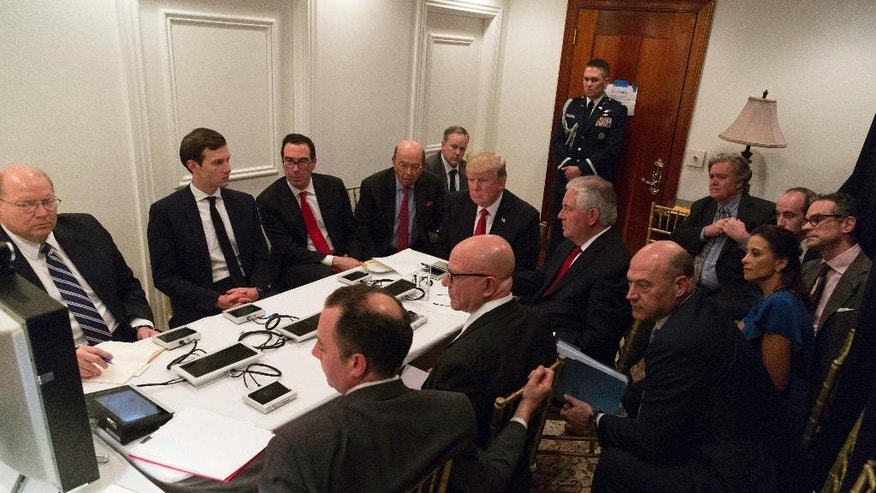 In this image provided by the White House, President Donald Trump receives a briefing on the Syria military strike from his National Security team, including a video teleconference with Secretary of Defense, Gen. James Mattis, and Chairman of the Joint Chiefs of Staff, Gen. Joseph Dunford, on Thursday, April 6, 2017, in a secured location at Mar-a-Lago in Palm Beach, Fla. (Shealah Craighead/The White House via AP)
