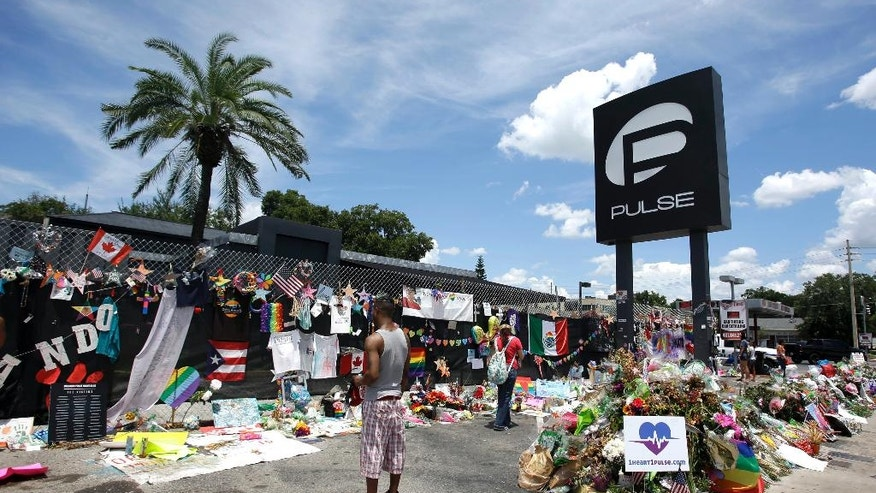 FILE - In this July 11, 2016, file photo, visitors at a makeshift memorial outside the Pulse nightclub, the day before the one month anniversary of a mass shooting, in Orlando, Fla. The FBI has been reviewing the handling of thousands of terror-related tips and leads received over the last three years to make sure they were properly investigated and that no obvious red flags were missed, The Associated Press has learned. It follows attacks by people once on the FBI's radar but who in the last 12 months are accused of massacring innocents in an Orlando nightclub, injuring people on the streets of New York, and gunning down travelers in a Florida airport.  (AP Photo/John Raoux, File)