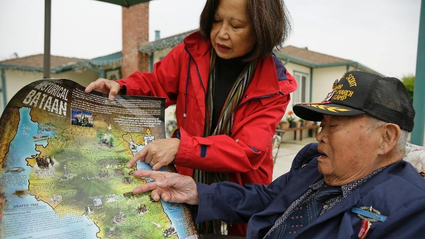 In this photo taken Thursday, April 6, 2017, Bataan Death March survivor Ramon Regalado looks over a map showing where he marched with Cecilia Gaerlan outside his home in El Cerrito, Calif. Survivors of the infamous Bataan Death March in the Philippines are marking the anniversary Saturday in San Francisco with speeches and a 21-gun battery salute to the thousands who died in it. Among the speakers will be Regalado, a former wartime machine-gun operator who turns 100 this month and is among the war's few living survivors. (AP Photo/Eric Risberg)