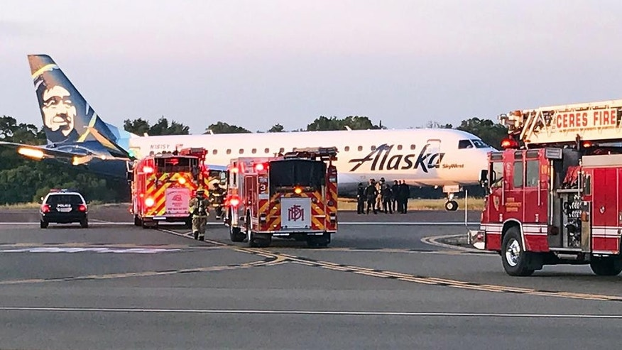 This photo provided by the Modesto, Calif., Fire Department shows an Alaska Airlines Embraer 175 twin jet after it made an unscheduled landing at the Modesto airport Sunday, April 9, 2017. Authorities said the flight headed from Sacramento to San Diego was forced to make the unexpected landing after a warning light indicated a possible fire in the plane's cargo area. It landed without incident in Modesto on Sunday. (Modesto Fire Department via AP)