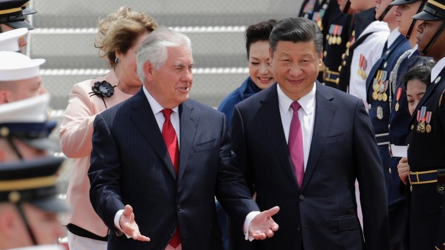 In this April 6, 2017, photo, Secretary of State Rex Tillerson, left, walks with Chinese president Xi Jinping at the Palm Beach International Airport in West Palm Beach, Fla. Lambasted for his low-key diplomacy, Tillerson is emerging from the shadows with his leading public role in shaping and explaining the Trump administration's missile strikes in Syria. He now takes on an even higher-profile mission, heading to Moscow this week under the twin clouds of Russia's alleged U.S. election meddling and its possible support for a Syrian chemical weapons attack. (AP Photo/Lynne Sladky)