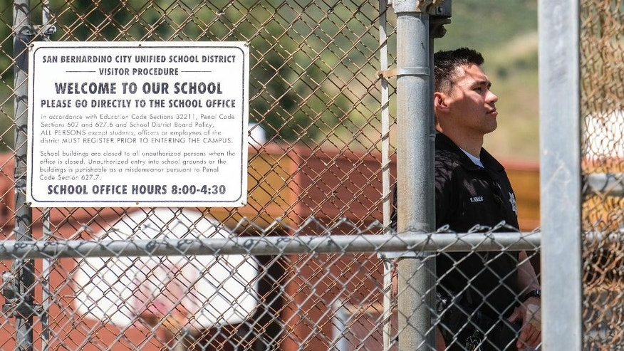 A police officer stands guard outside North Park School after a fatal shooting at the elementary school, Monday, April 10, 2017, in San Bernardino, Calif. (AP Photo/Ringo H.W. Chiu)
