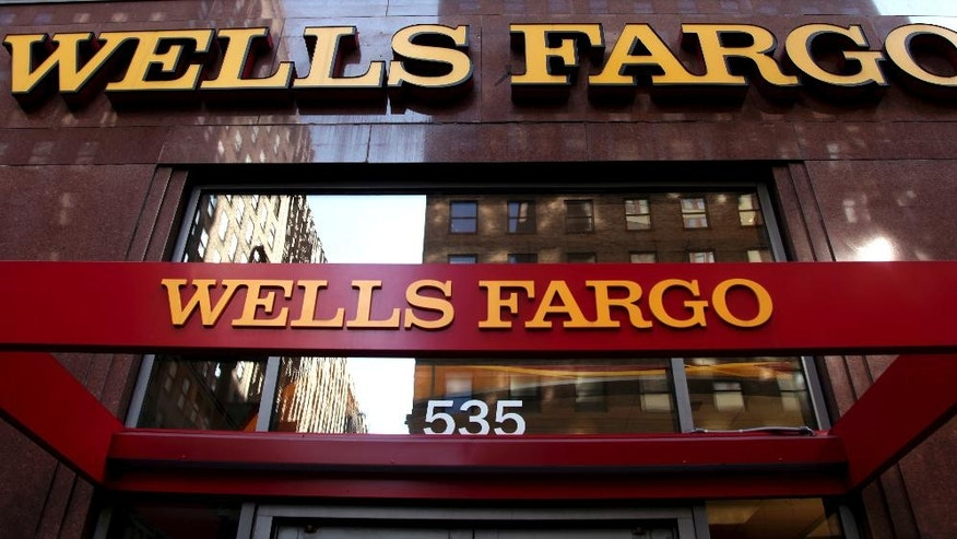 "FILE - In this May 6, 2012, file photo, a Wells Fargo sign is displayed at a branch in New York. In the results of an investigation released Monday, April 10, 2017, Wells Fargo's board of directors has blamed the bank's most senior management for creating an ""aggressive sales culture"" at Wells that eventually led to the bank's scandal over millions of unauthorized accounts. (AP Photo/CX Matiash, File)"