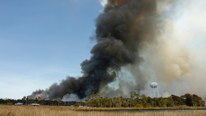 In this Saturday, April 8, 2017 photo, aircraft from the U.S. Forestry Service and the Florida Forestry Service work to contain a massive wildfire in Hernando Beach, Fla