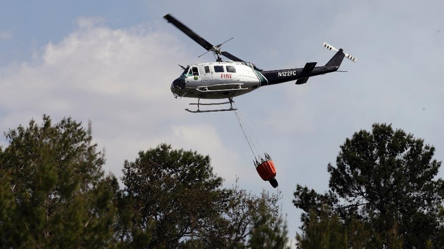 A Florida Division of Forestry helicopter drops a bucket of water on a wildfire Tuesday, April 11, 2017, in Hudson, Fla. Florida Gov. Rick Scott has declared a state of emergency as more than 100 wildfires actively burn statewide. (AP Photo/Chris O'Meara)
