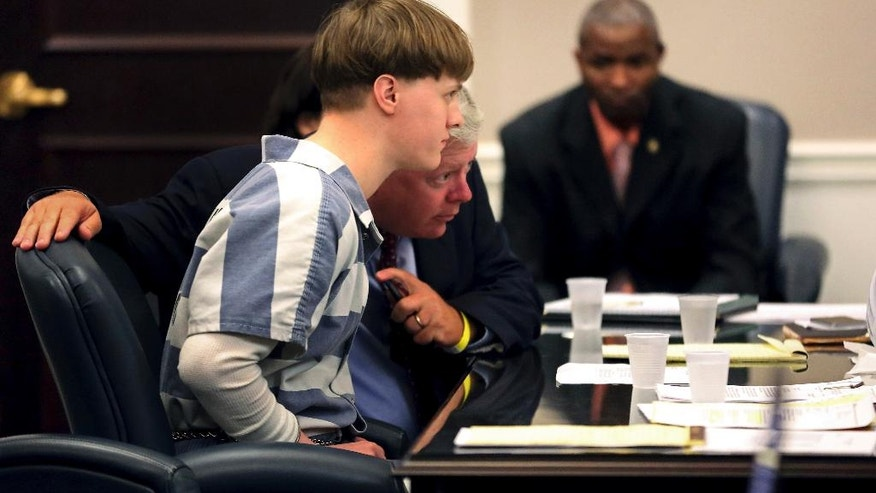 Bill McGuire of the S.C. Commission on Indigent Defense, talks with Dylann Roof as he appears in the Charleston County Court Monday, April 10, 2017, to enter his guilty plea on murder charges in Charleston,S.C. The convicted Charleston church shooter, Roof was given nine consecutive life sentences in state prison after he pleaded guilty to state murder charges Monday, leaving him to await execution in a federal prison and sparing his victims and their families the burden of a second trial. (Grace Beahm/The Post And Courier via AP, Pool)