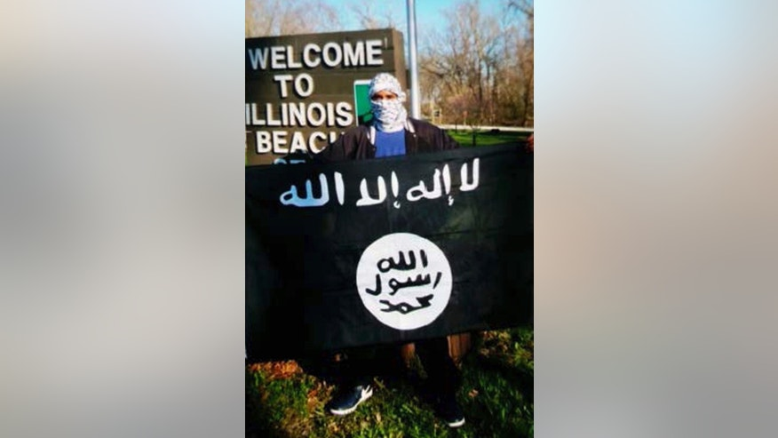 In this undated photo provided by the Federal Bureau of Investigation, Joseph D. Jones poses with an Islamic State group flag at Illinois Beach State Park in Zion, Ill.  Jones and Edward Schimenti were arrested by FBI agents on Wednesday, April 12, 2017 on terrorist charges for allegedly conspiring to support the Islamic State militant group. (FBI via AP)