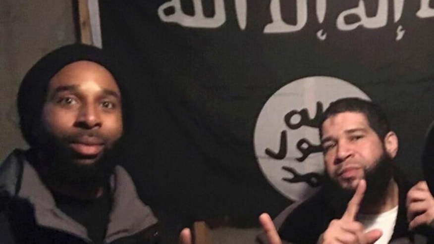 In this undated photo provided by the Federal Bureau of Investigation Joseph D. Jones, left, and Edward Schimenti pose in front of an Islamic State group flag. Jones and Schimenti were arrested by FBI agents on Wednesday, April 12, 2017 on terrorist charges for allegedly conspiring to support the Islamic State militant group. (FBI via AP)