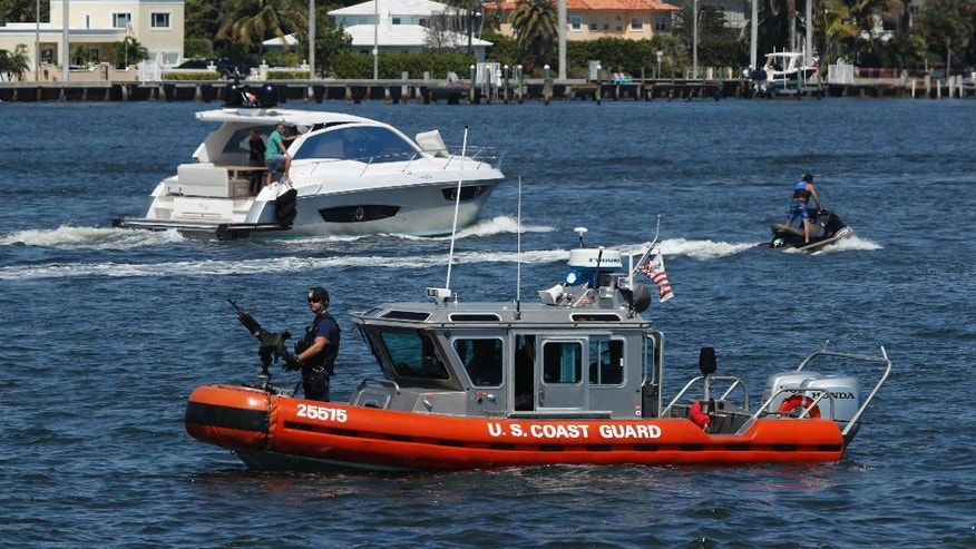 FILE - In this March 19, 2017 file photo, U.S. Coast Guard patrol Lake Worth Lagoon as President Donald Trump returns to his Mar-a-Lago estate in Palm Beach, Fla. It's widely estimated that each trip to the resort costs taxpayers $3 million, based on a government study of the cost of a 2013 trip to Florida by President Barack Obama. But that trip was more complicated and the study's author says it can't be used to calculate the cost of Trump's travel. This weekend, Trump is making his seventh visit to Mar-a-Lago since becoming president.  (AP Photo/Manuel Balce Ceneta, File)