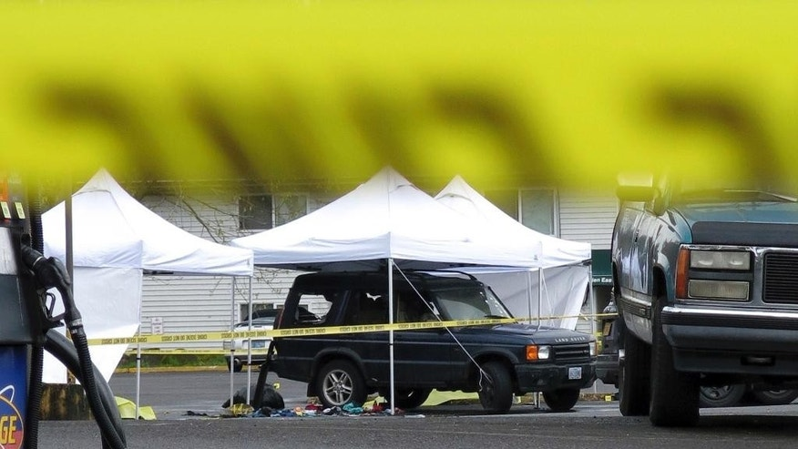 CORRECTS CITY TO GRESHAM -  Police tape surrounds an vehicle after a shooting in Gresham, Ore, Wednesday, April 12, 2017.  A man and his two young daughters have died after police got word he was threatening the girls, leading to a shootout with officers. (AP Photo/Gillian Flaccus)