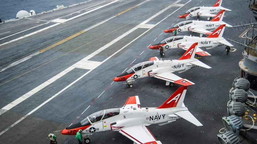 FILE - In this Dec. 10, 2016 file photo, pilots perform pre-flight procedures in T-45C Goshawks from Training Air Wing One on the flight deck of the aircraft carrier USS George Washington docked in Norfolk, Va.