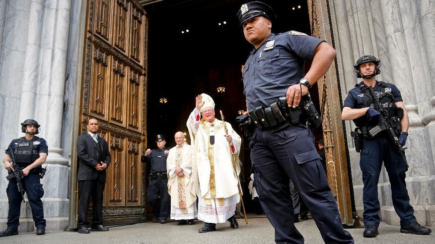 Cardinal Timothy Dolan, center, surrounded by NYPD anti-terror unit, appears briefly following Mass to wave at crowds mingling for the Easter parade Sunday April 16, 2017, in New York. (AP Photo/Bebeto Matthews)